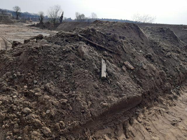Na pierwszym planie znajduje się usypana hałda ziemi z której wystają odpadyw postaci deski, w tle drzewa