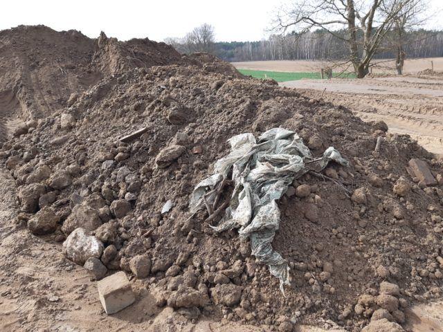 Hałda ziemi z odpadami na polu, w oddali widać drzewa