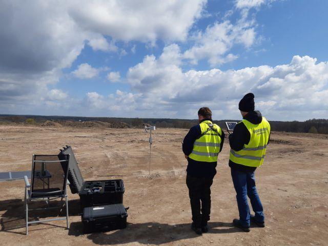 Dwie osoby stojące na otwartej przestrzeni w żółtych kamizelkach przeprowadzją kontrolę przy użyciu dronów. Po lewej stronie obok stolika z krzesłem stoi otwarta skrzynka na drony