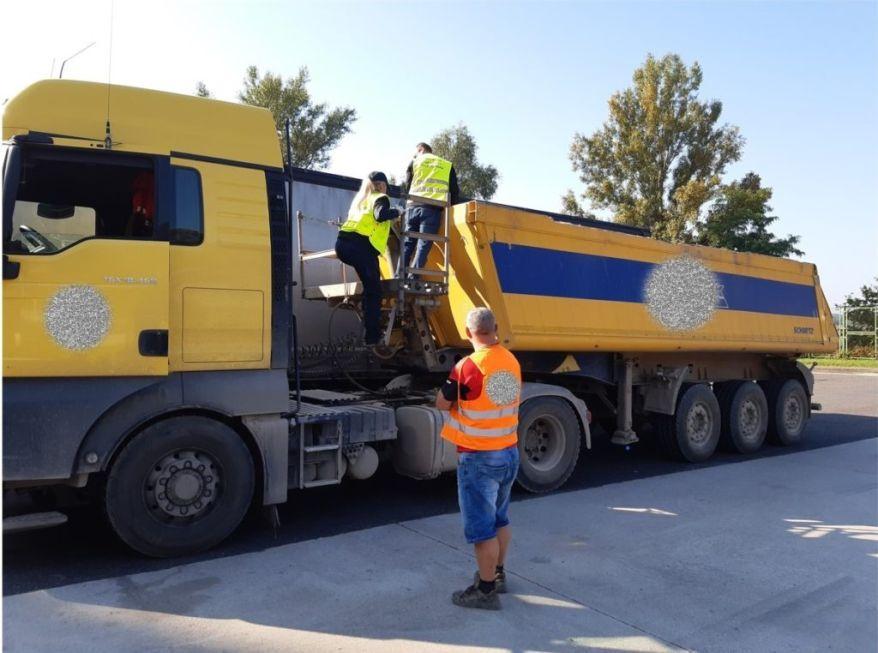 Mężczyzna w pomarańczowej odblaskowej kamizelce stoi na placu przed żółtym samochodem ciężarowym, na naczepę ciężarówki wchodzi kobieta i mężczyzna ubrani w żółte odblaskowe kamizelki