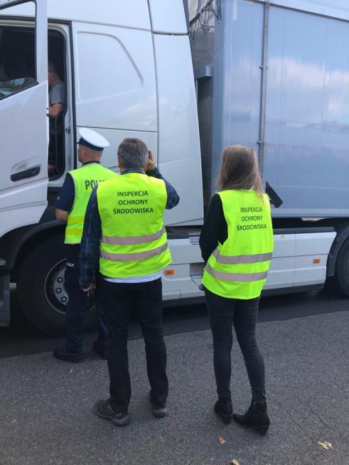 Troje ludzi w odblaskowych kamizelkach stoi przed otwartą kabiną samochodu ciężarowego