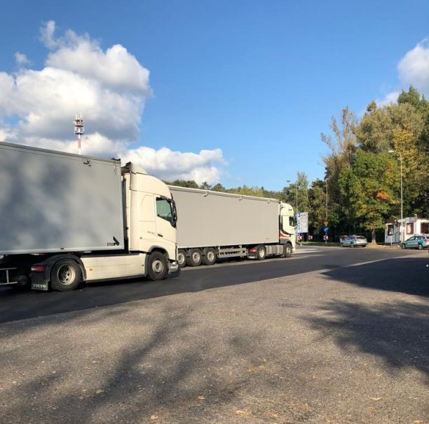 Parking na którym stoją dwa samochody ciężarowe, w tle samochody osobowe służb kontrolnych