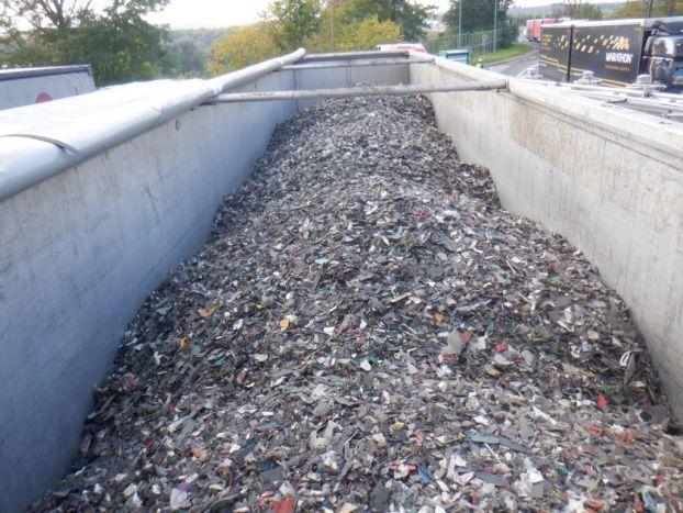Naczepa samochodu ciężarowego wypełniona sypkim odpadem w postaci plastiku, gumy, metali